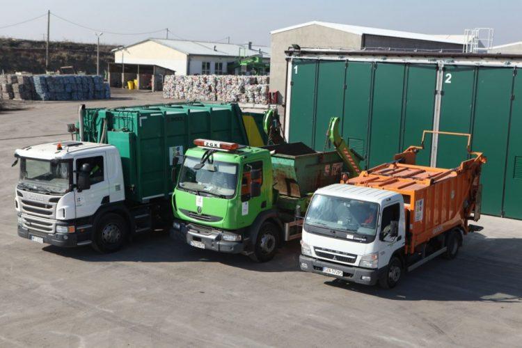 3 samochody ciężarowe- biało-zielona śmieciarka, zielony kontenerowiec oraz biało- pomarańczowy kontenerowiec