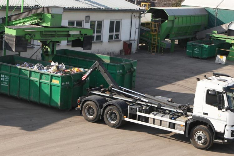 Biały samochód (kontenerowiec) wraz z zielonym kontenerem. W tle biały budynek