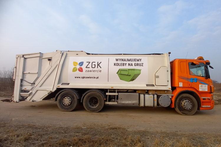 Samochód ciężarowy typu śmieciarka. Biała zabudowa i pomarańczowa kabina