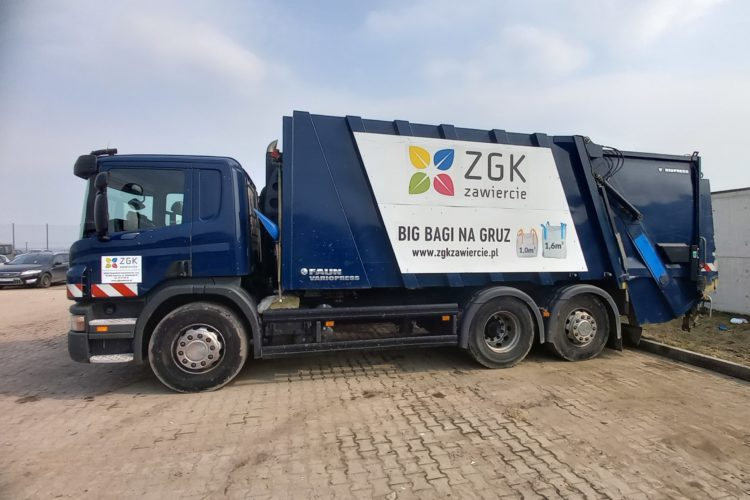 Granatowy samochód ciężarowy typu śmieciarka